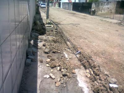 Rua com lama e buracos