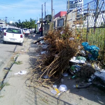 Muito lixo na calçada de um terreno baldio
