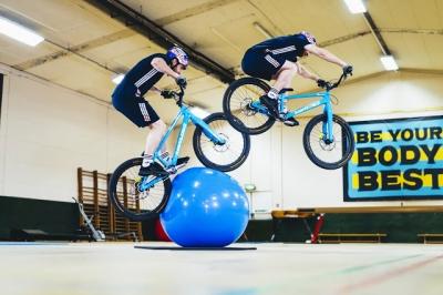 Ciclista demonstra suas habilidades dentro de uma academia