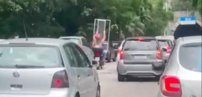 Mulher é flagrada na garupa de moto carregando uma janela no Rio