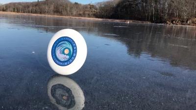 Jogando um frisbee em um lago congelado, o que acontece?