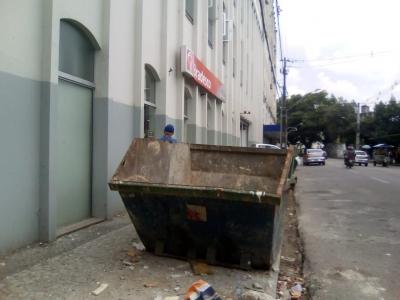 Caçamba em cima da calçada