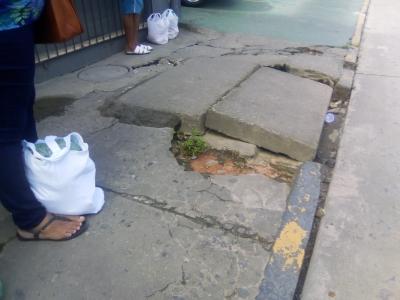 Calçada danificada e rede entupida