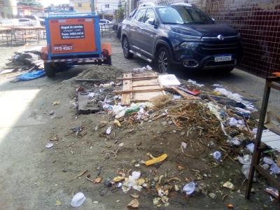 Buraco, lixo e carros na calçada